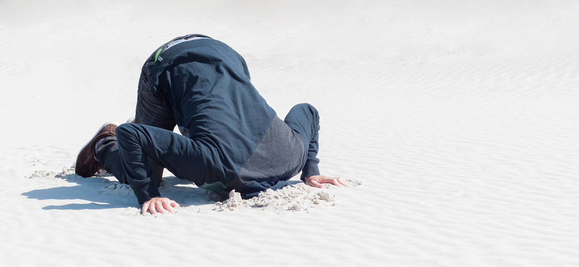 Young male (student) hiding head in sand because of excessive labor.